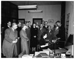 Officials watch with interest a document being prepared in the bursar's office, 1949